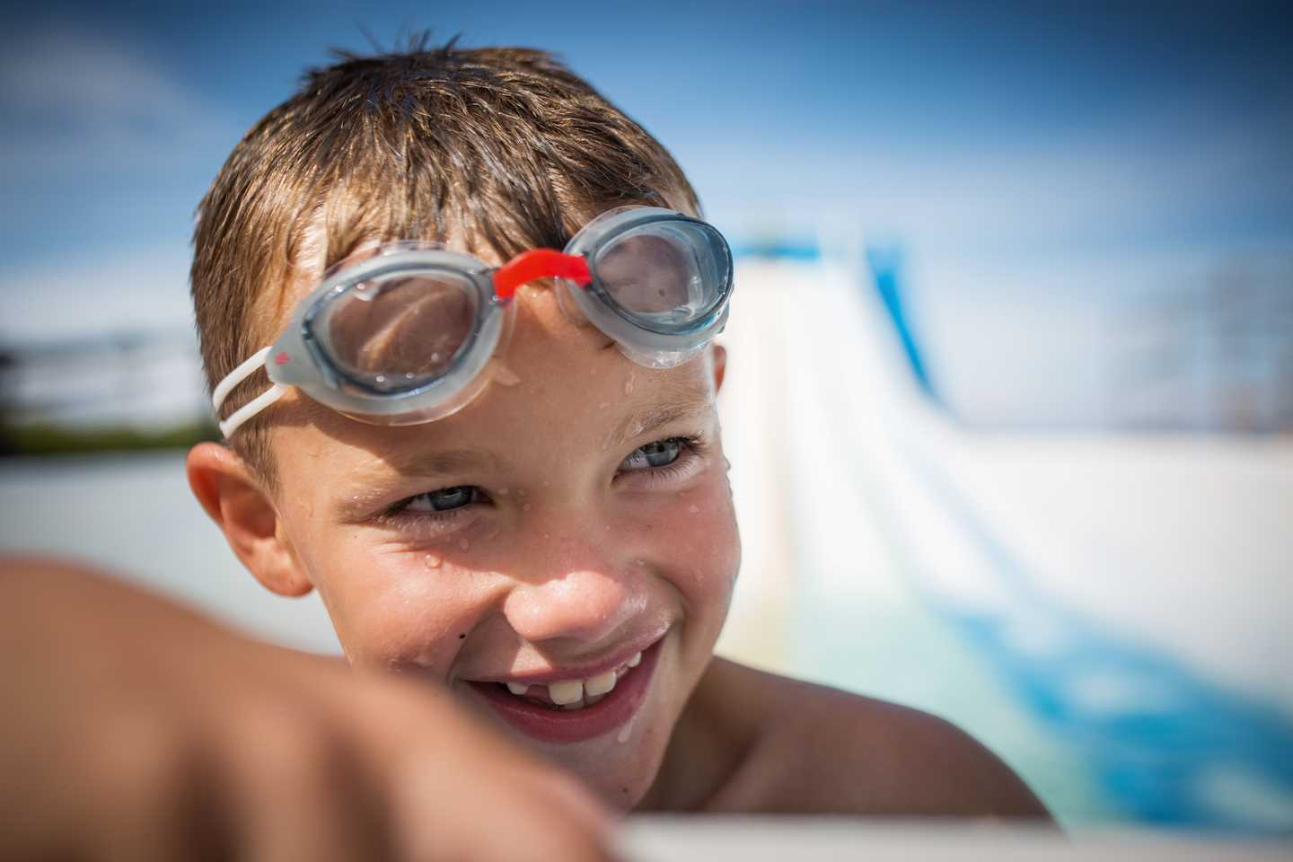 A child with goggles in the outdoor pool