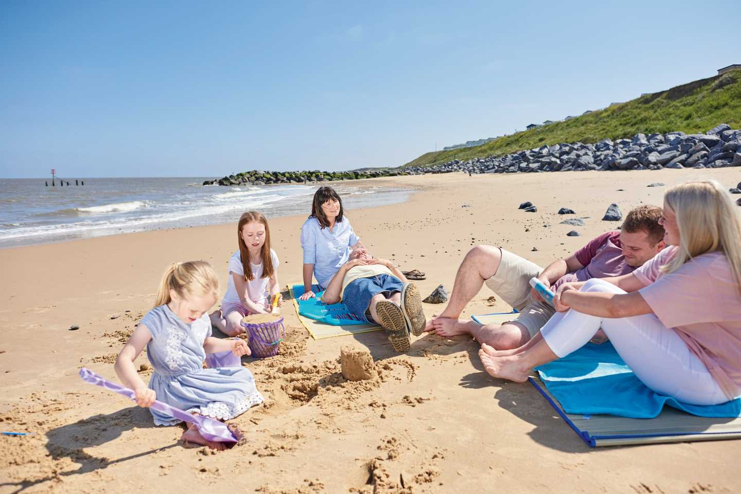 Family relaxing on the beach at Hopton