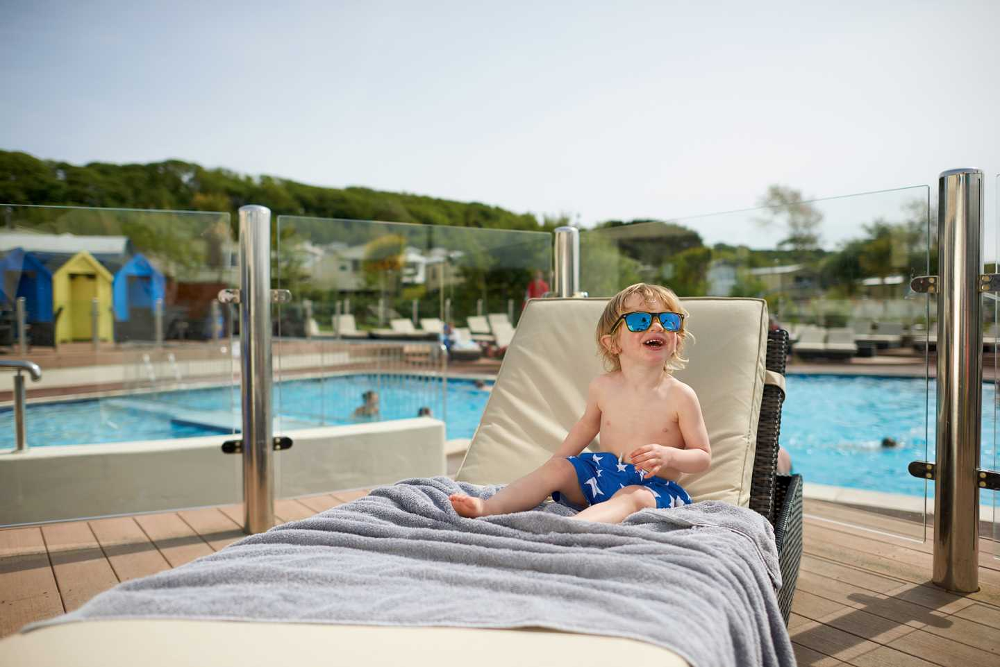 Child laying on the sun lounger by the outdoor pool