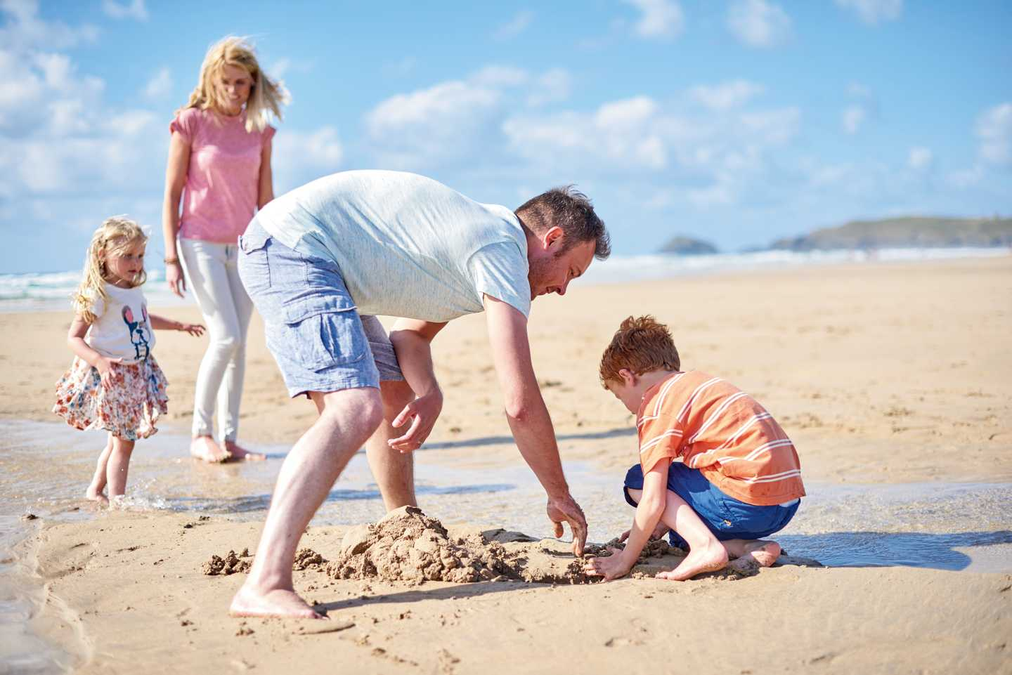 Family building sandcastles on a beach in Cornwall