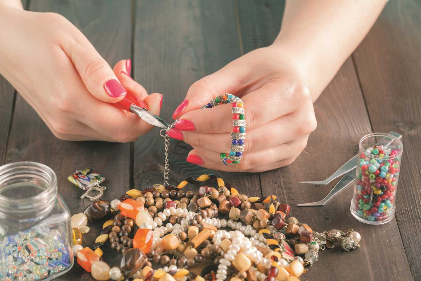 A lady with a pile of beads in front of her whilst holding a bracelet she is making