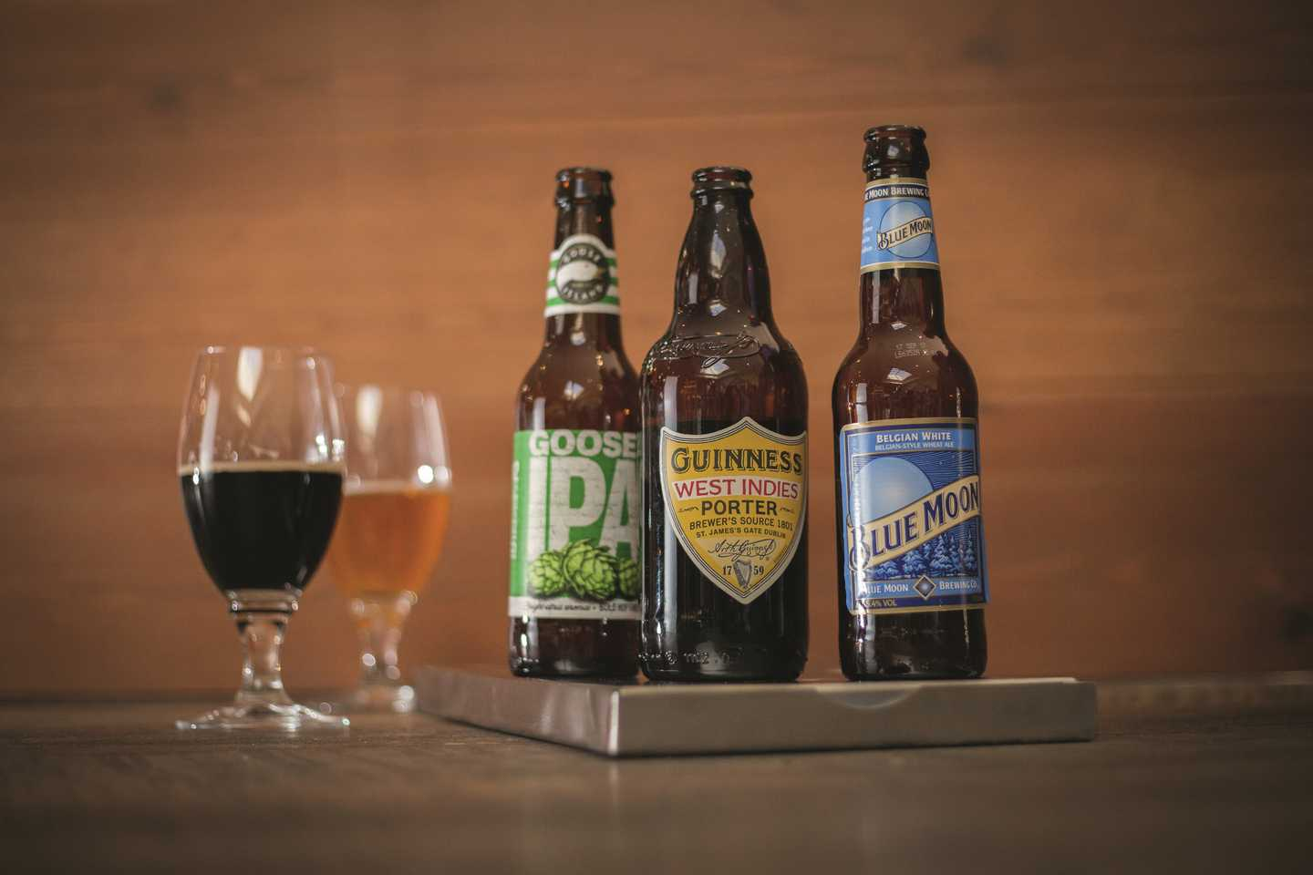 A selection of three beers and ale bottles with two beer glasses