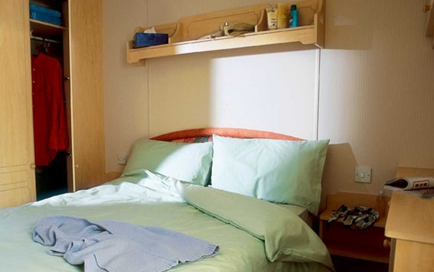 A Comfort Plus chalet master bedroom with double bed, wardrobe, side cabinet and shelf above the bed