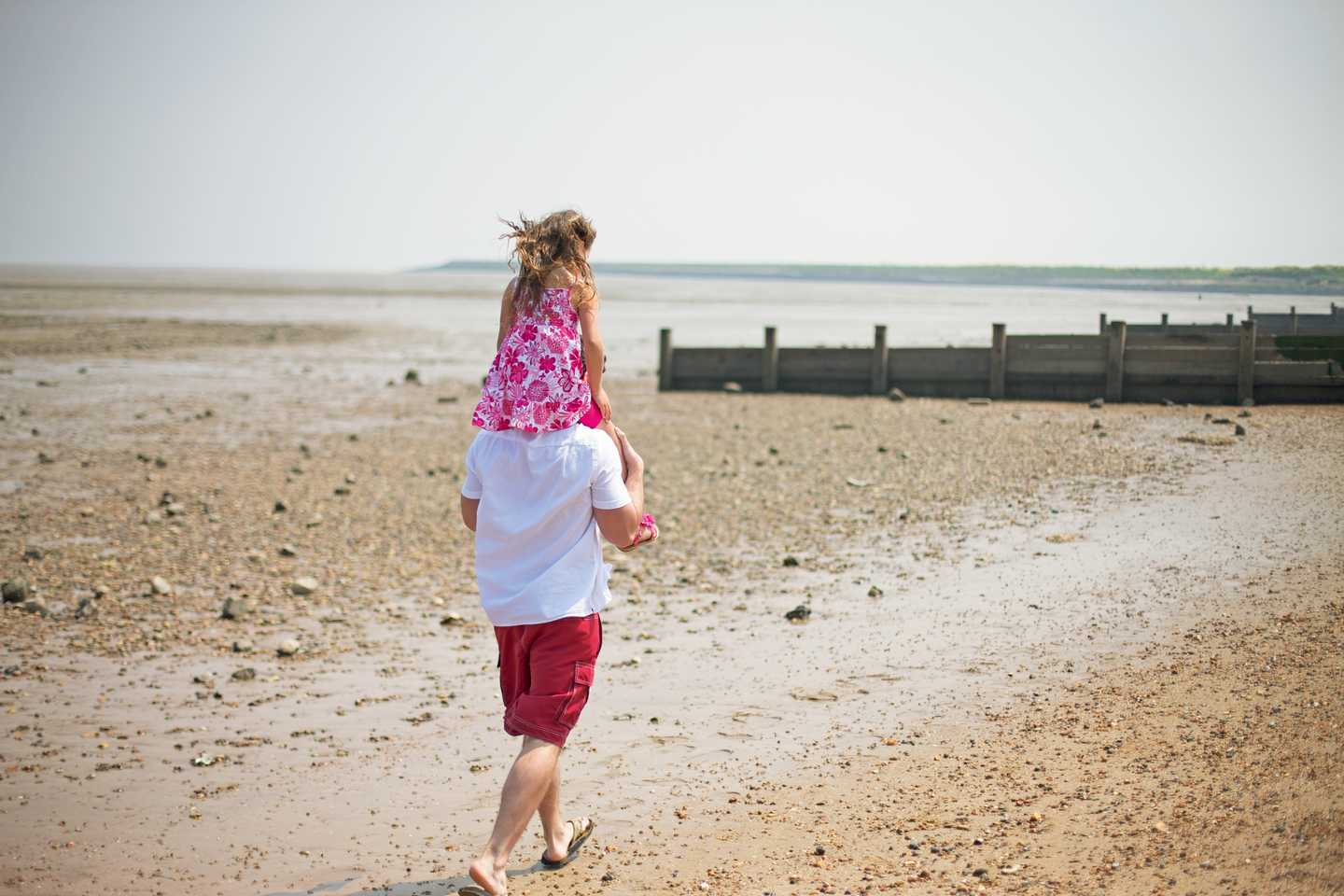 A man walking along the river with his Daughter on his shoulders near Allhallows