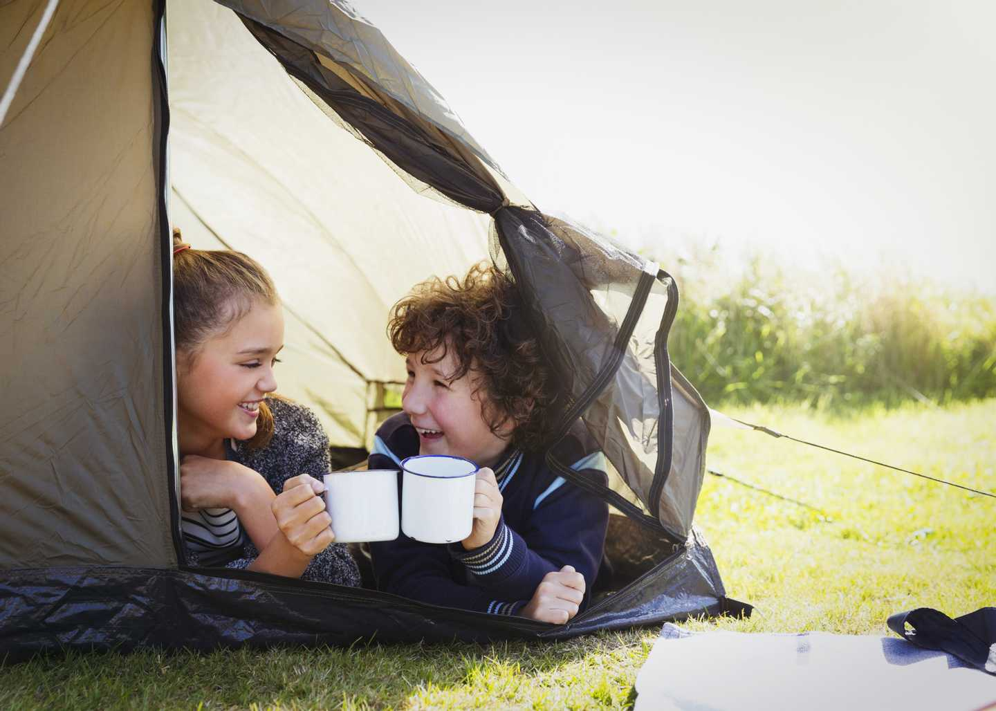 A pair of children in a tent enjoying a hot chocolate
