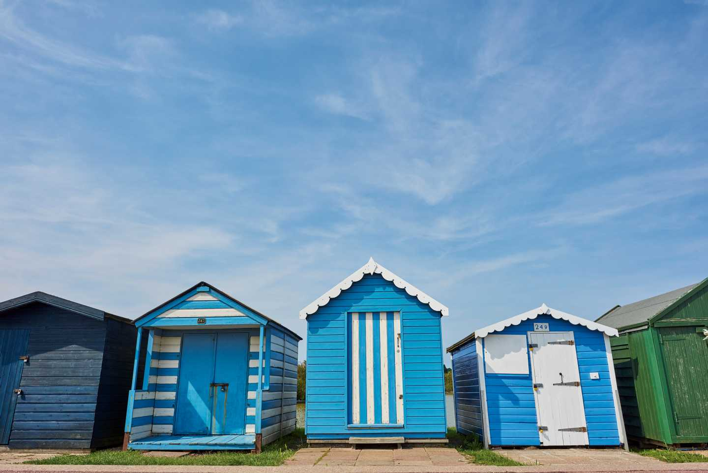 A row of blue beach huts at Brightlingsea
