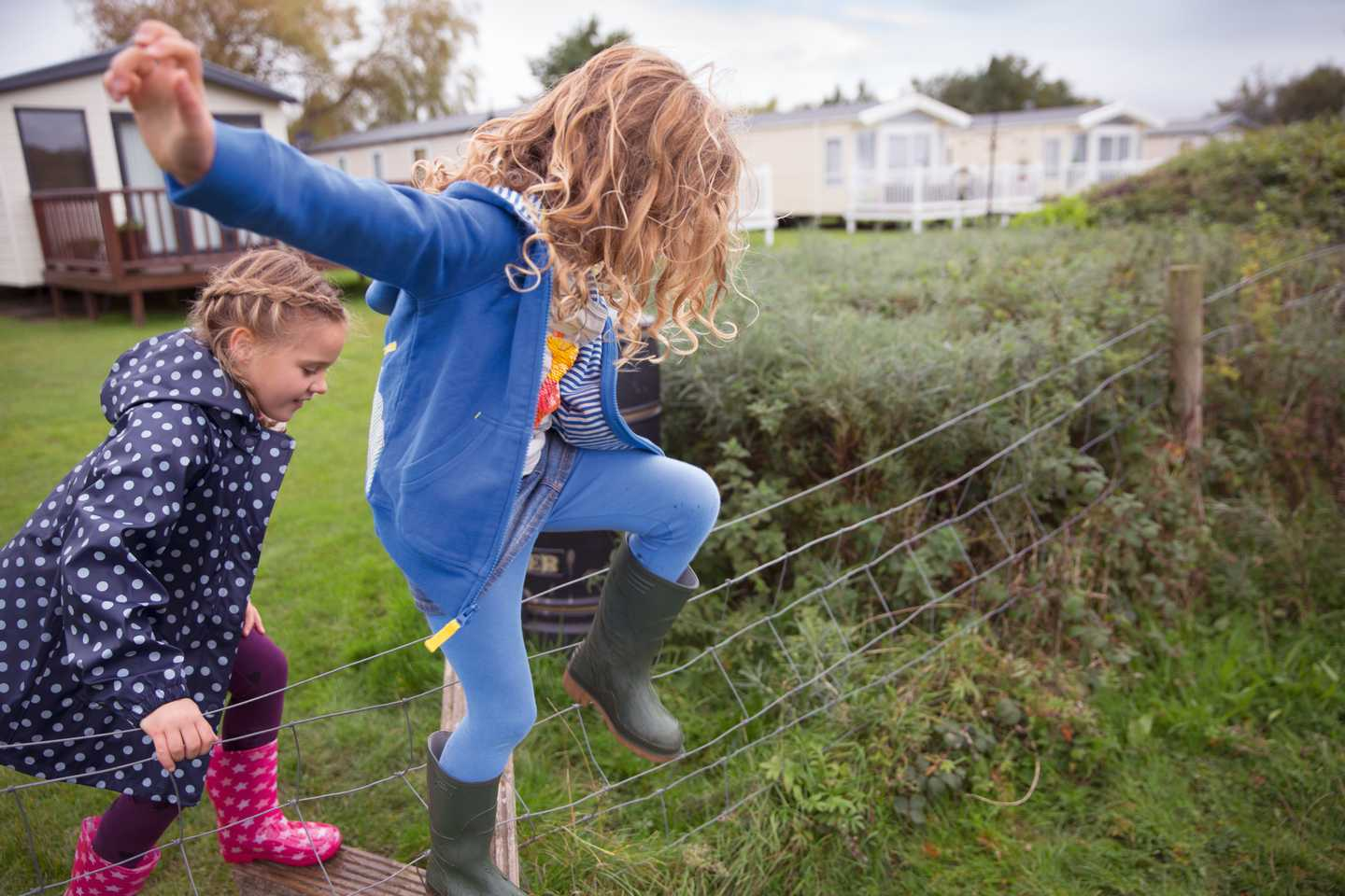 Girl and boy with wellies stamping through the grass