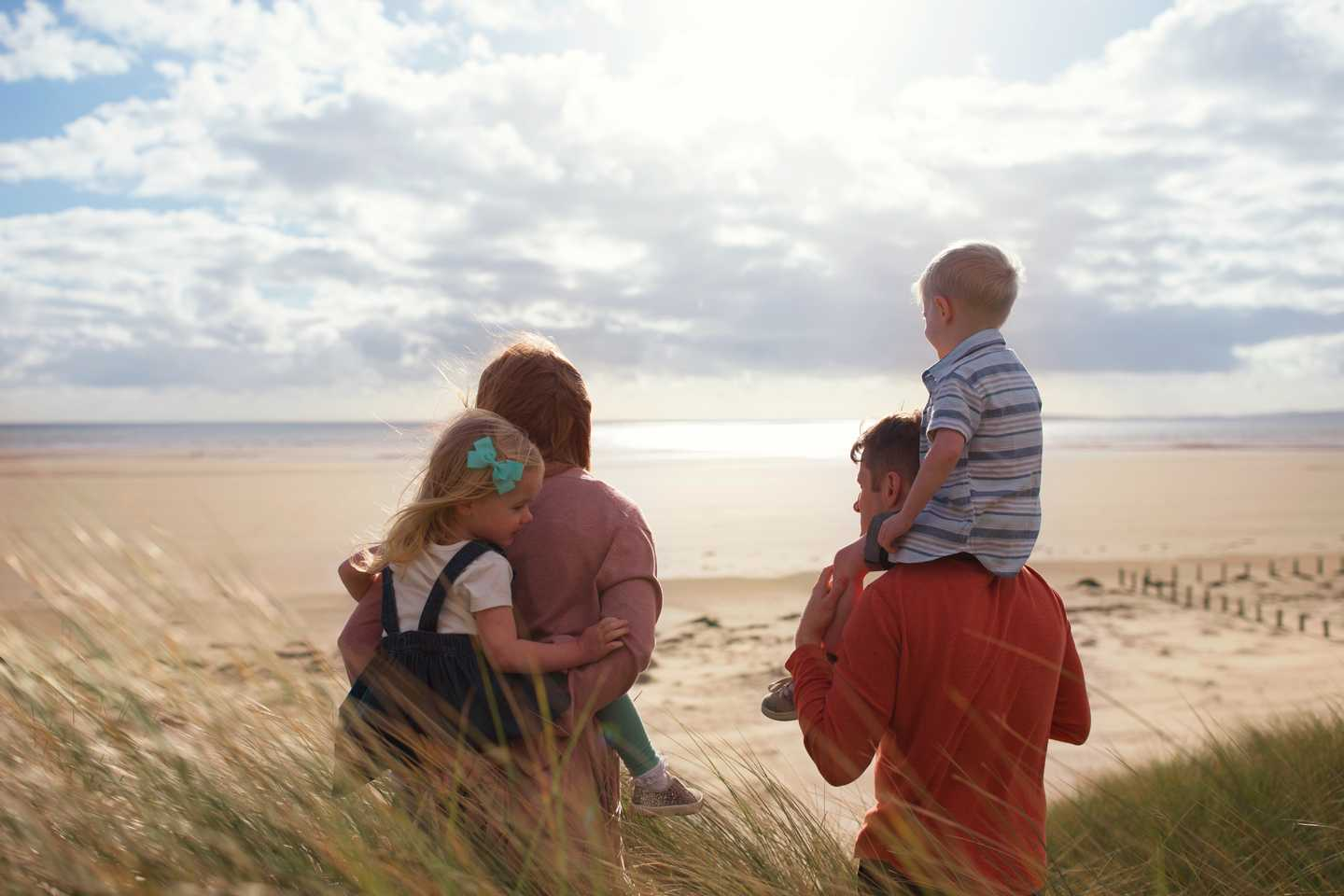 A family on the beach looking out to the sea