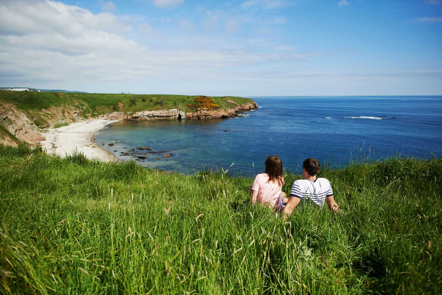 A couple taking a clifftop walk by the sea at Berwick Holiday Park