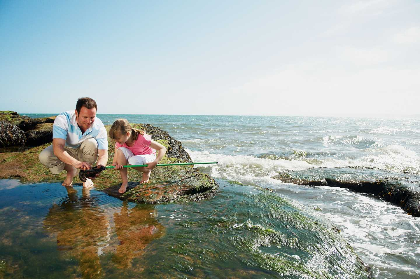 A father and daughter rock pooling along the Devon coast