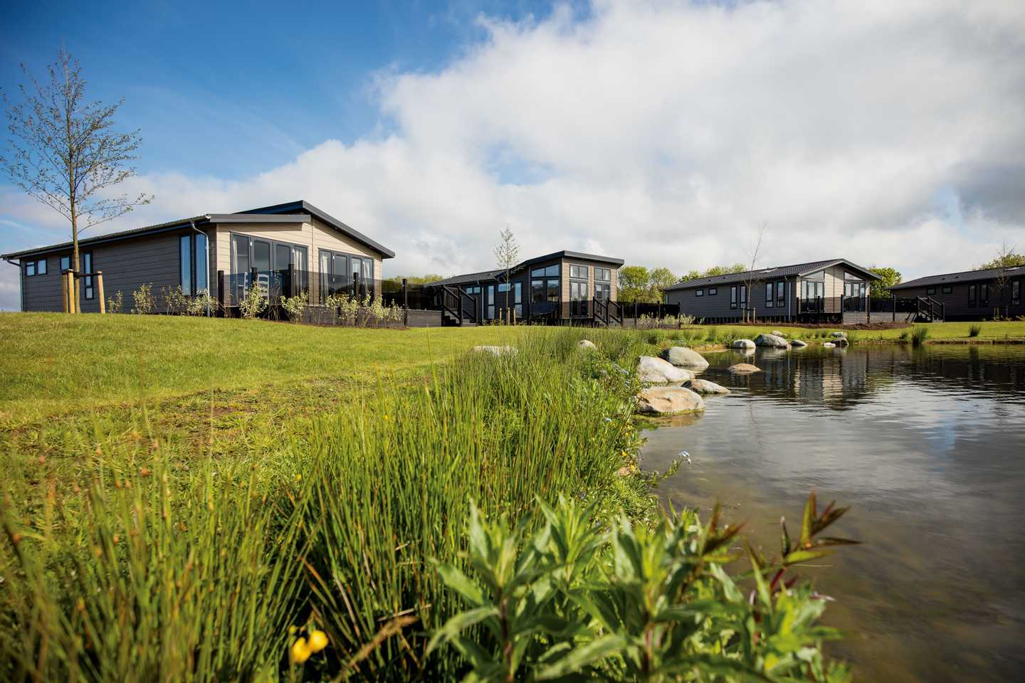 A view from the rocky, natural lake of luxurious lodges with verandas