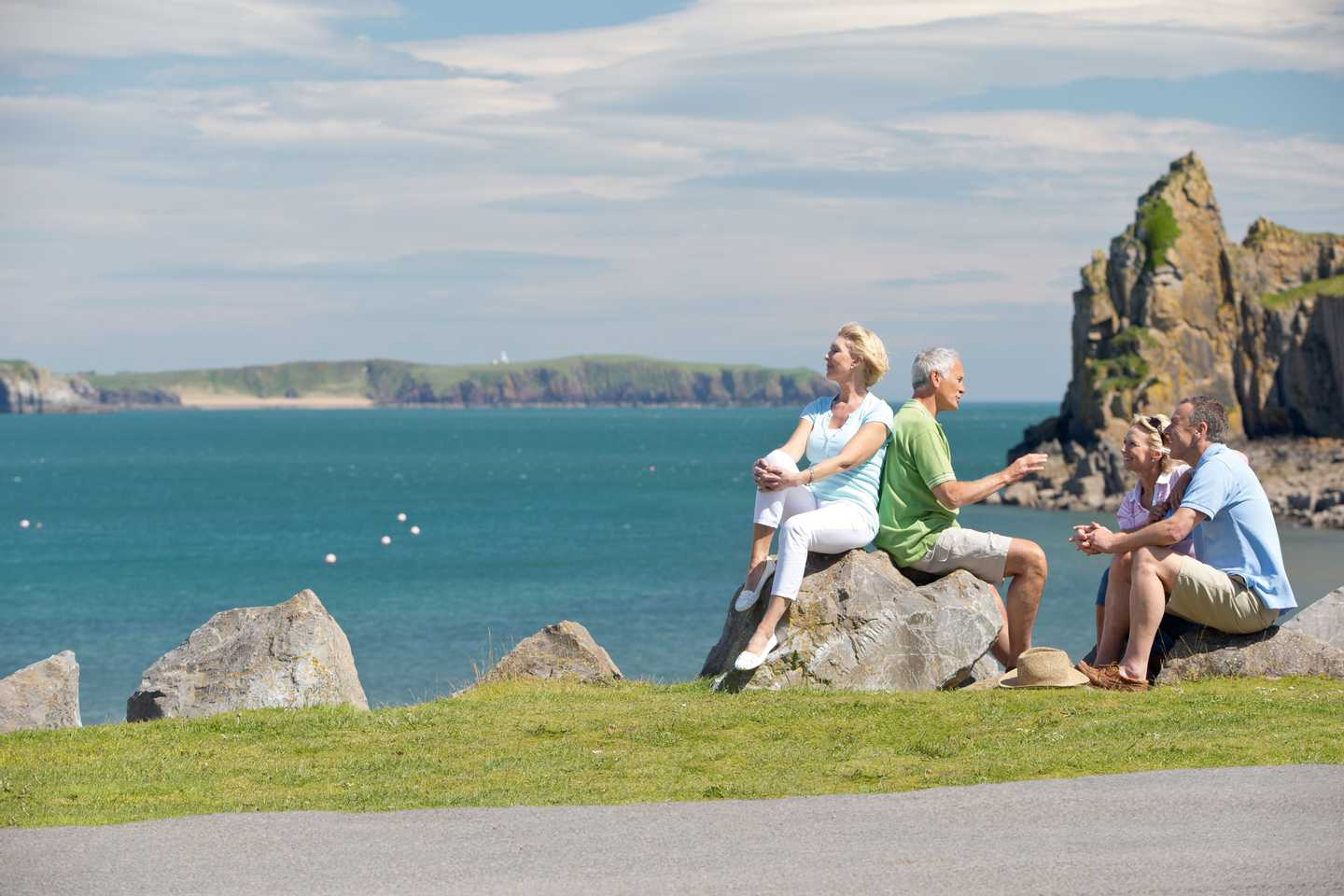 A group of friends perched on giant stones as they take in the scenic view across the sea in Tenby