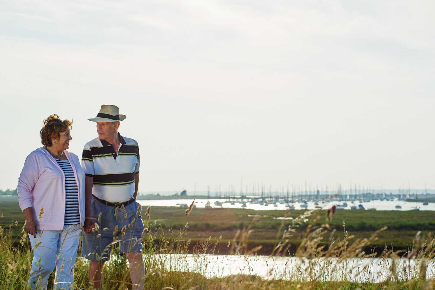 An older couple taking a walk through the marshlands near the park with boats in the background