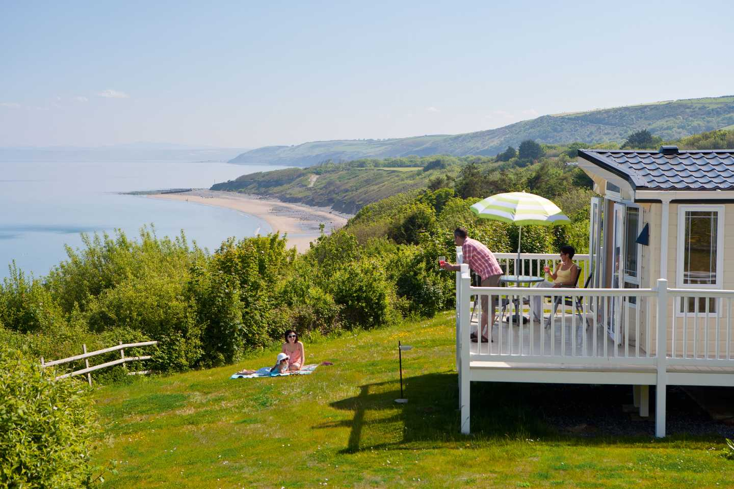 A view across the bay with clear blue skies at Quay West Holiday Park with a caravan and veranda in the foreground
