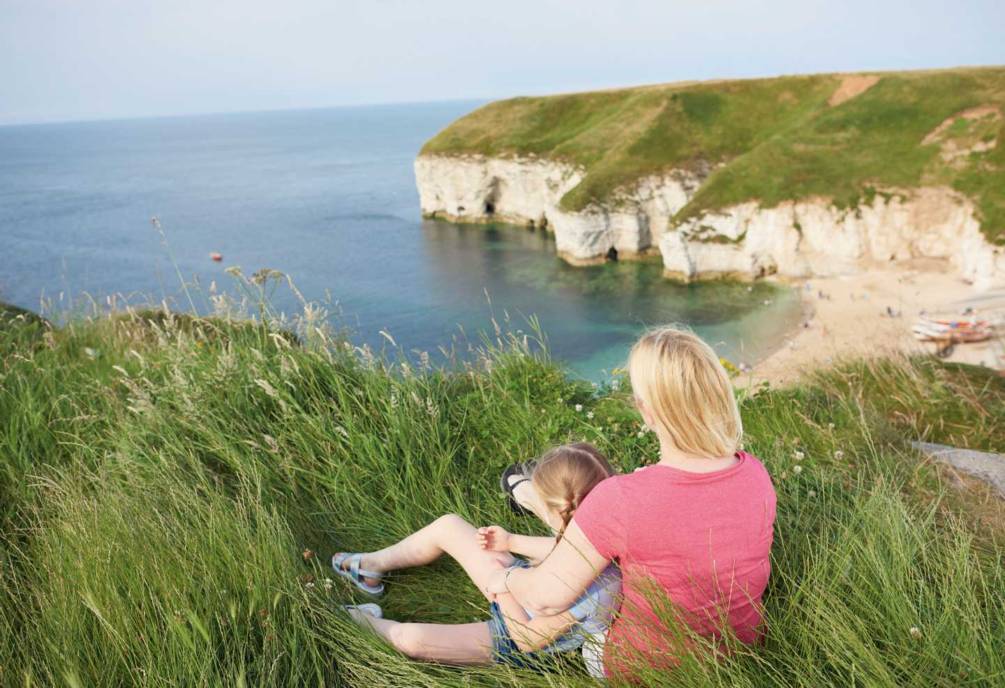 A mother and daughter sitting on a grassy area at the top of a cliff at Thornwick Bay Holiday Village overlooking the beach in a bay below