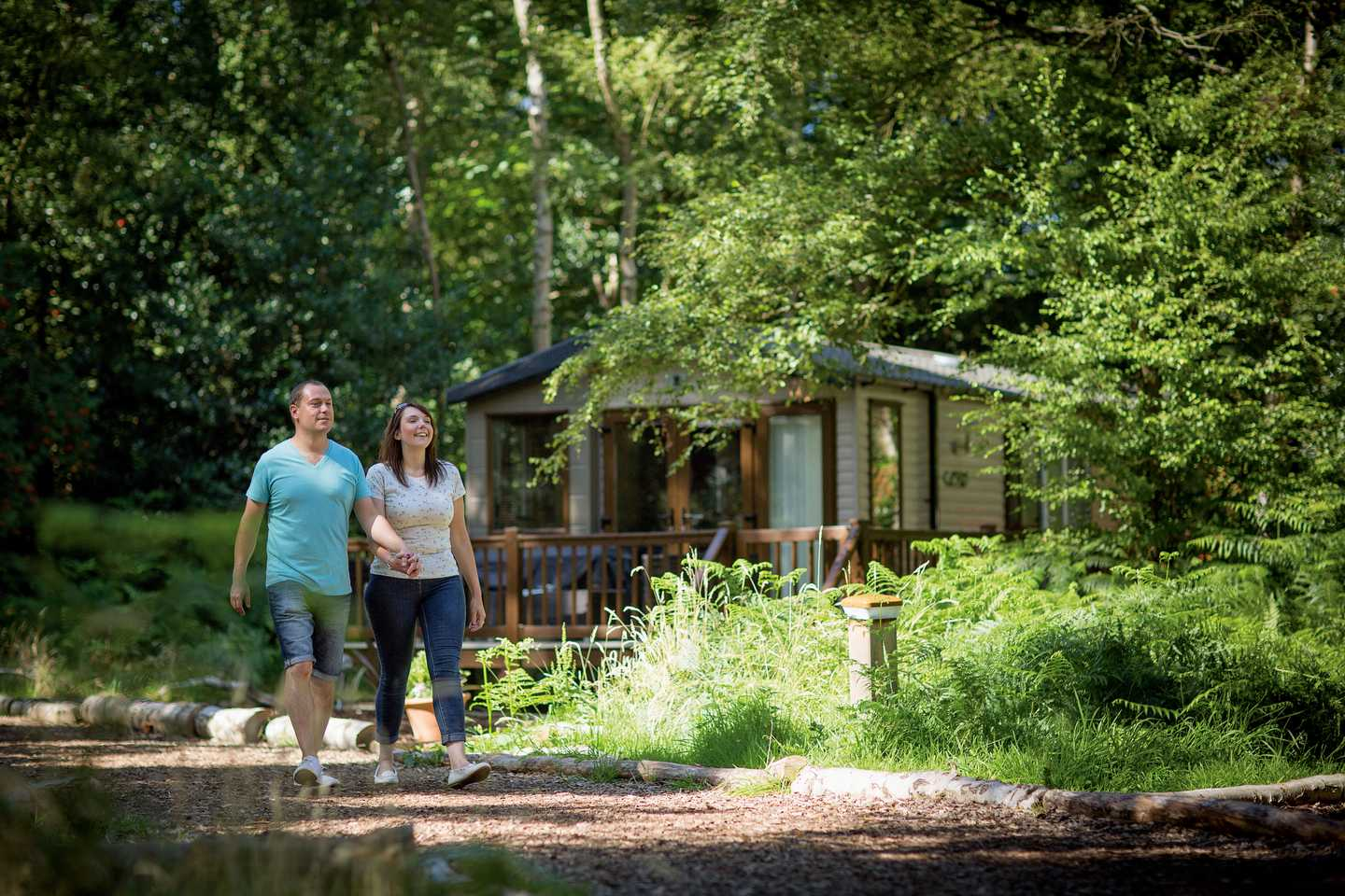 A couple walking hand in hand through a wooded area of Wild Duck Holiday Park with ferns on the ground and a caravan with veranda in the background