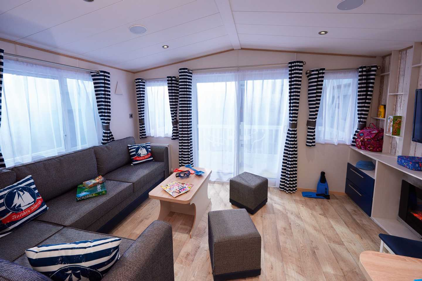 A Platinum with Decking caravan lounge with sofa, coffee table, foot rests and decking