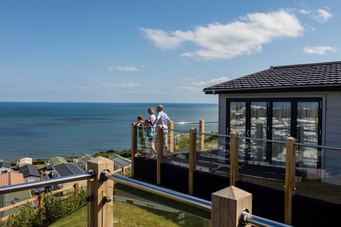 A family looking out to sea on a Luxury Lodge decking