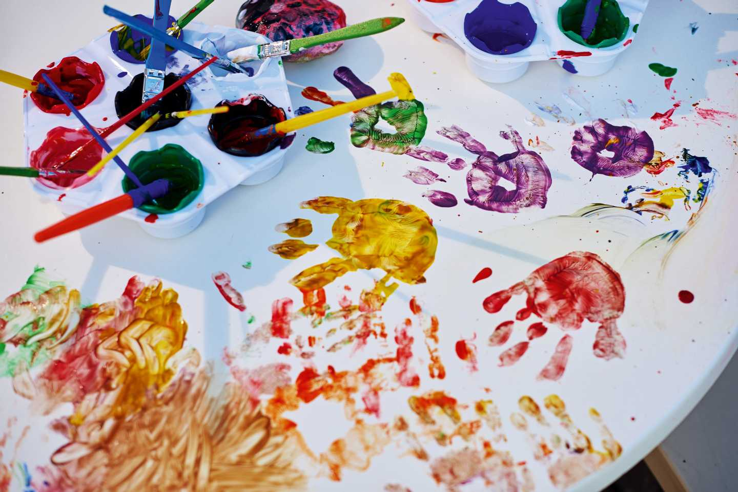 Paints and hand prints on table