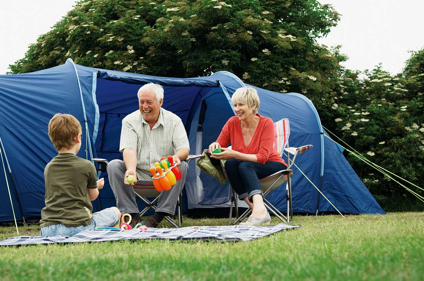A pair of guests sitting outside their tent talking and laughing